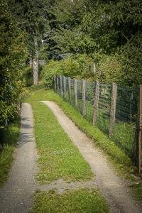 Schotterweg zwischen Gartenzäunen