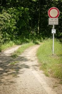 An Schild vorbei in den Wald